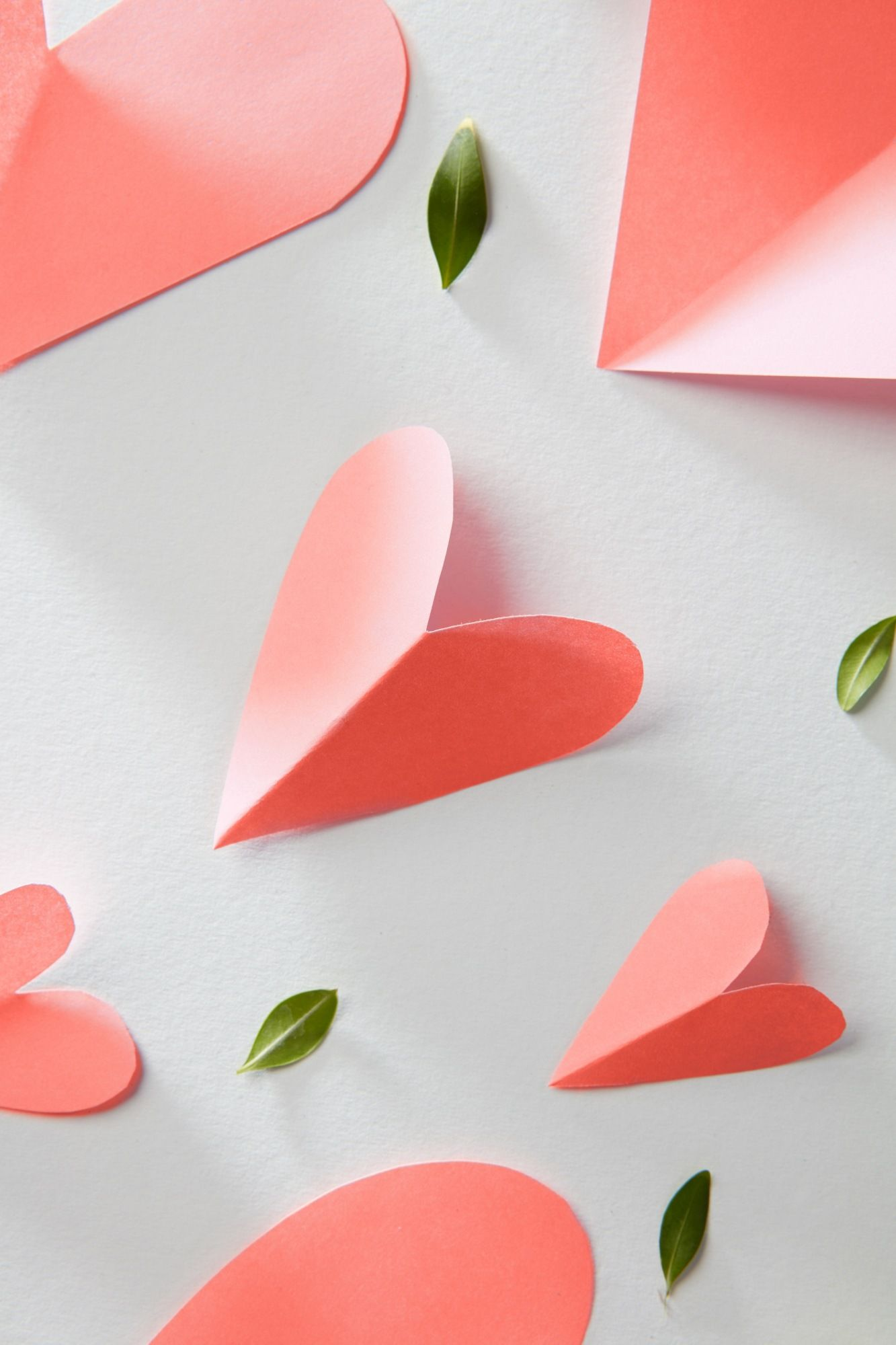 Greeting patter with valentines hearts in a color of the year 2019 Living Coral pantone on a white background, copy space.
